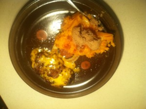 A plate of turkey burgers with sweet potatoes on the side.