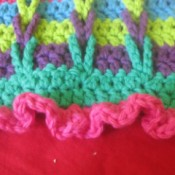 A multi colored crocheted scarf with connecting loops.