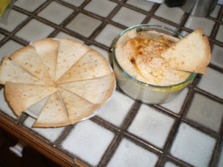 A bowl of homemade hummus, served with flavored tortilla chips.