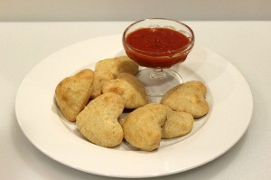 heart shaped calzones on plate with sauce for dipping