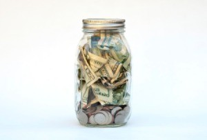 A jar full of bills and coins.