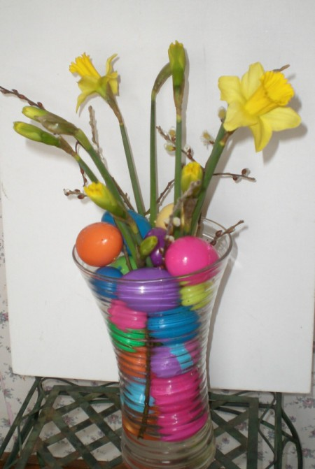 glass vase with daffodils and colored eggs