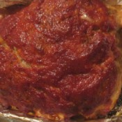 A meatloaf topped with chili sauce.