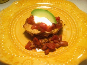 A dish of tamale pie, topped with salsa, sour cream and avocado.