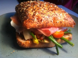 A prosciutto sandwich with several different vegetables.