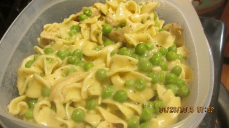 A main dish of chicken noodles and peas.