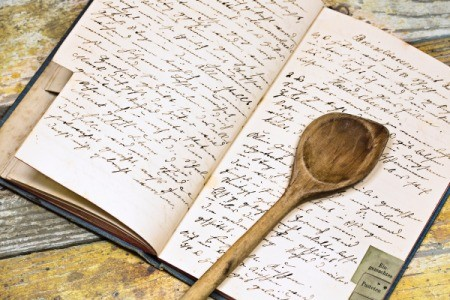 A recipe book with a wooden spoon.