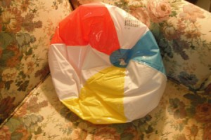 A deflated beach ball used as a wedge pillow.