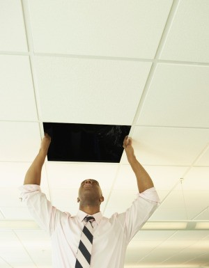 A man replacing a ceiling tile.