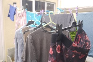 A row of clothing on hangers, drying on a clothesline.