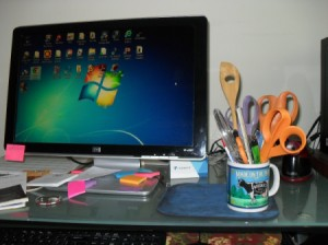 mug on computer table with scissors in it