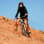 person mountain biking on red loam hill