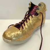 gold duct taped athletic shoe