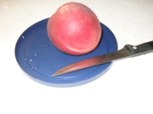 can lid with a peach and knife