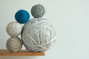 large ball of yarn with smaller ones stacked against it