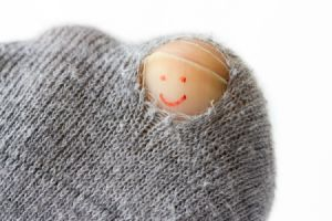hole in sock exposing big toe nail with smiley face