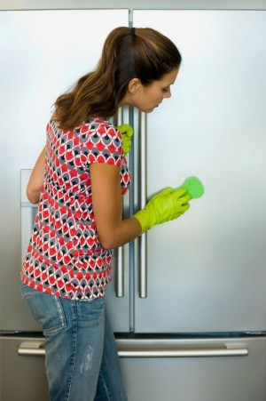 woman cleaning the outside of a refrigerator