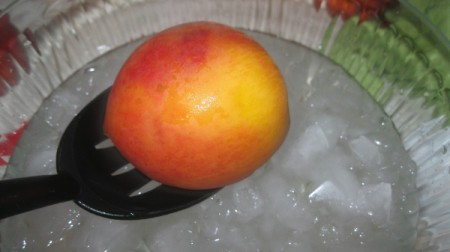 peach in slotted spoon