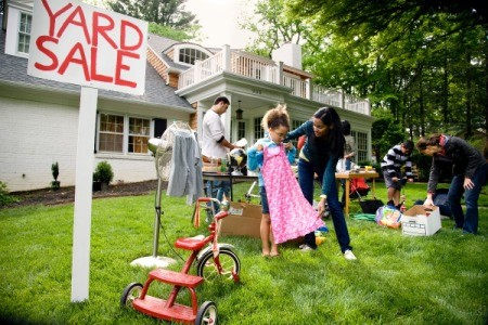 An active yard sale in the front yard of a house.