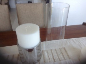 candle in holder with glass cover next to it