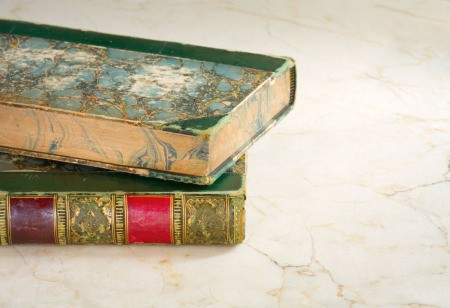 Two old ornate hardcover books.