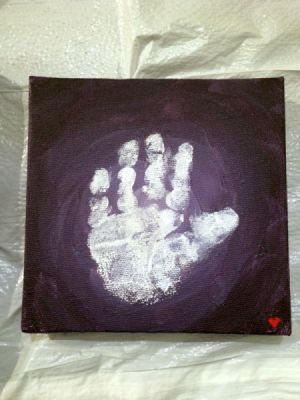 A child's white handprint on black paper.