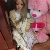 doll next to a pink stuffed bear