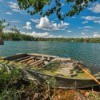 small boat on a lake with green algae on top and sides