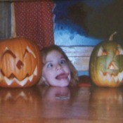 Three kids posing with jack o'lanterns