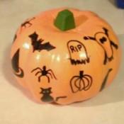 A foam pumpkin with marking pen decorations.