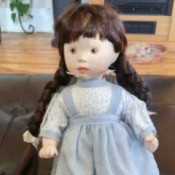 dark haired doll wearing white dress with a blue pinafore over it