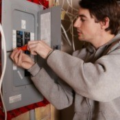 man working on breaker box