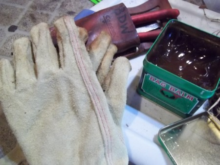 gardening gloves and open can of bag balm