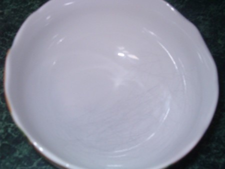 A white bowl with scratches removed on one side.