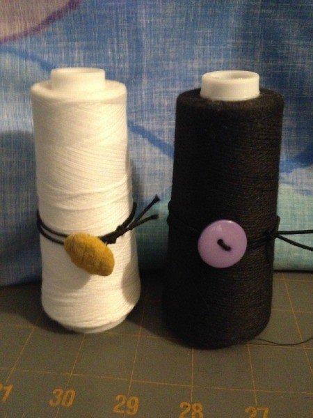 Using Large Spools on a Sewing Machine - large spool of white and one of black thread fitted with button and elastic