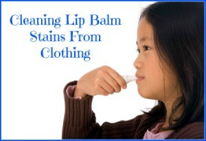 A girl putting on lip balm.