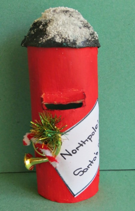 A paper tube Santa mailbox, colored red.