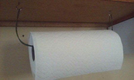 A paper towel holder made from a clothes hangar.