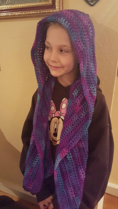 front view of child wearing a crochet hooded scarf with ends hanging down