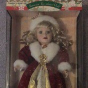 doll in fancy red cape with white fur trim