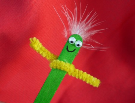 green stick puppet with yellow pipe cleaner arms