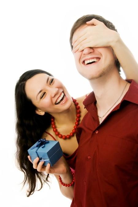A girlfriend giving her boyfriend a gift.