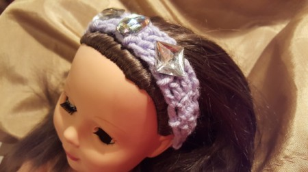 A crocheted headband on an American girl doll.