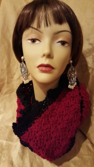 A burgundy and black scarf displayed on a mannequin head.