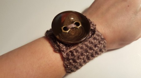 A crocheted bracelet with a large brown button.