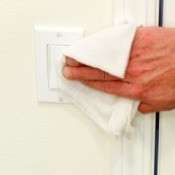 Cleaning a lightswitch near a door.