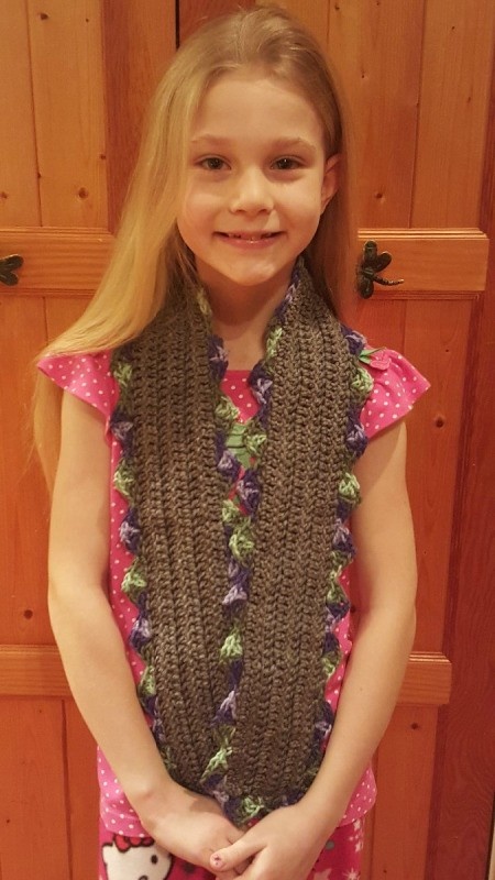 A girl with a brown crocheted scarf with a scallop patten.