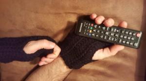 Crochet Men's Fingerless Gloves - person wearing gloves using a remote
