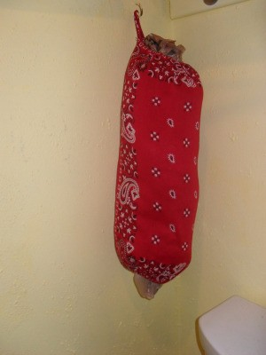 A storage tube for plastic bags made from bandanas.