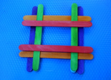 placing a red stick across the green ones and inline with the blue sticks below